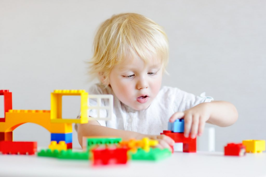 Cute little boy playing with colorful plastic blocks-